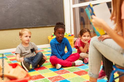 Fototapeta Gruppe Kinder hört aufmerksam zu beim Vorlesen obraz na płótnie