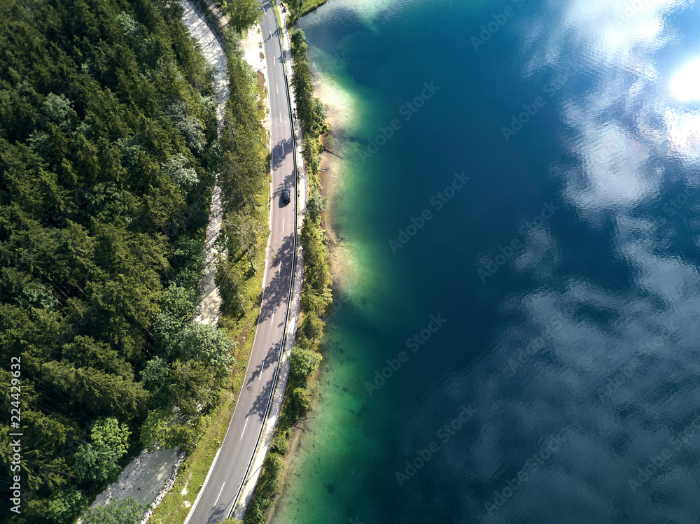 Aerial view of the road near the lake and the forest from above