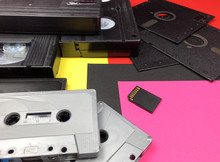 Tapes, Floppy Disk And Memory Card On Colorful Background. Old And Modern Technology.