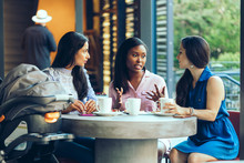 Female Friends Talking While Sitting In Coffee Shop