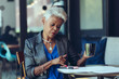 Senior businesswoman using smartphone while having coffee in office