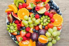 Healthy Fruit Platter, Strawberries Raspberries Oranges Plums Apples Kiwis Grapes Blueberries On The Dark Grey Wooden Table, Top View, Close Up, Selective Focus