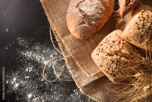 Assortment of bread on sackcloth and flour on black table