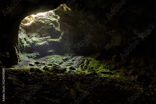 Fotografie, Obraz  Dark cave with a bright daylight spot of exit