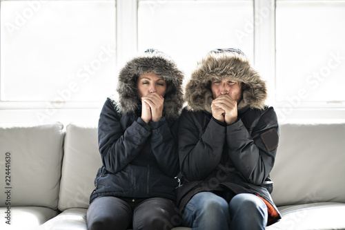 Couple have cold on the sofa at home with winter coat Canvas Print