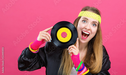 Woman in 1980's fashion holding a record on a pink background