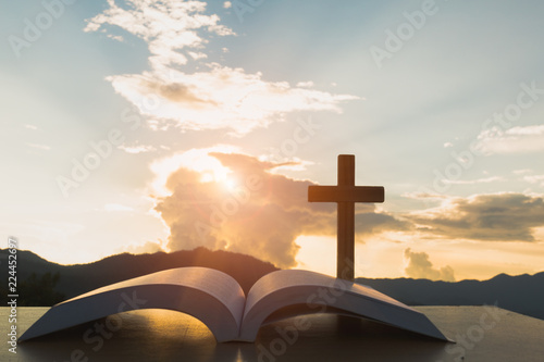 Photo open Bible, script in blur with focus on palm cross,on sunrise background, Crucifix, Symbol of Faith