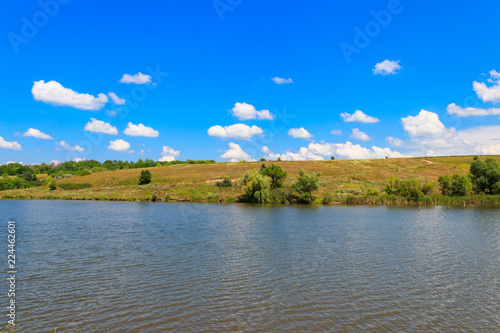 Fotobehang Meer / Vijver Summer landscape with beautiful lake, green meadows, hills, trees and blue sky