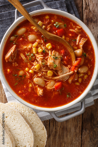 Brunswick Stew - thick, flavorful and hearty one-pot stew with vegetables and meat on a chicken broth and BBQ sauce close-up in a bowl. Vertical top view