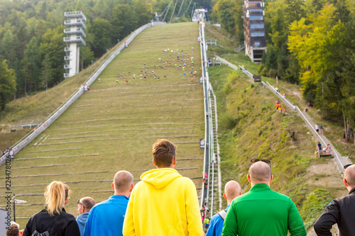 Spectators on sport event cheering for conmpetitors running upwards on ski jump.
