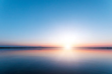 Beautiful, Red Dawn On The Lake. The Rays Of The Sun Through The Fog. The Blue Sky Over The Lake, The Morning Comes, The Sky Is Reflected In The Water.