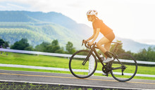 Cycling Competition,cyclist Athletes Riding A Race At High Speed On Road Way, Sports Women Bikes In The Morning,vintage Color,selective Focus, Sports Concept,low Angle View,Business Competition