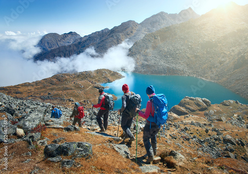 Fototapeta Group tourists with Backpacks descends down on Mountain Trail during Hike. obraz