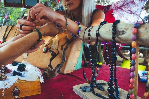 A woman selling homemade craft jewelry from a market stall at a hippy festival Canvas