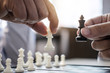 Businessman's hand playing chess game to development analysis new strategy plan, business strategy leader and teamwork concept for win and success