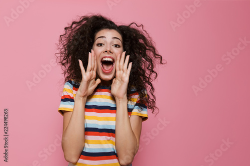 Fotografía  Image of young woman 20s with curly hair shouting or calling, isolated over pink