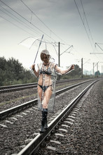 A Woman In A Transparent Raincoat And Underwear With An Umbrella On The Tracks Of The Railway.