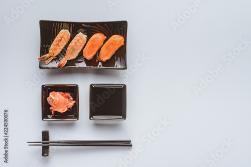 Fotografia  top view of delicious sushi with salmon and shrimp, ginger, soy sauce and chopst