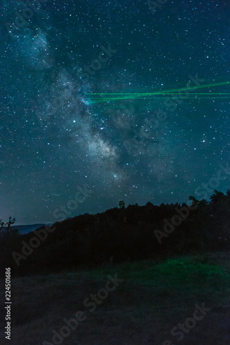 Fototapeta Milky Way over the mountains and laser pointers from astronomers
