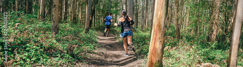 Fototapeta Young woman and man participating in a trail race through the forest obraz