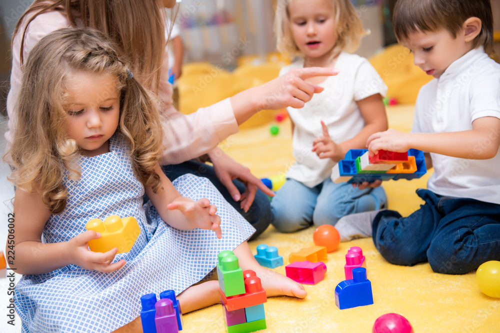 Fototapety, obrazy: cropped image of educator pointing on something to kids playing with constructor in kindergarten