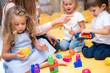 Leinwandbild Motiv cropped image of educator pointing on something to kids playing with constructor in kindergarten
