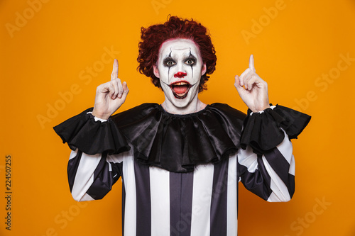 Happy clown man 20s wearing black costume and halloween makeup looking at camera Fotobehang