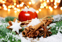 Moody Christmas Scene With Wooden Apple, Cinnamon Sticks, Cinnamon Stars, Anise Stars, Fir Branches, Snow And Blurry Lights In The Background