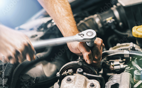 plakat Hands of car mechanic in auto repair service with wrench