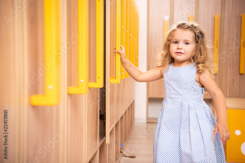 Obraz na plátně smiling adorable kid opening locker in kindergarten cloakroom and looking at cam