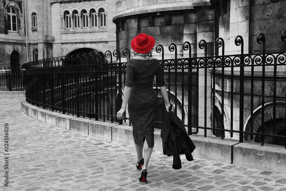 Fototapeta Young woman walking in Montmartre, Paris. Black and white photo with isolated red colour.