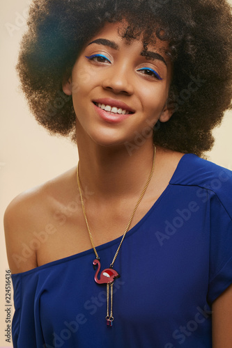 A close up portrait of a young African lady with short curly hair. The pretty girl in navy blue top, wearing blue eyeliner and red flamingo chain necklace, posing, looking at the camera, smiling.