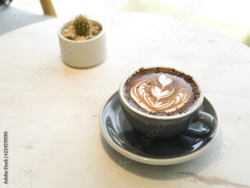 Staande foto Chocolade Hot chocolate latte art with dark color plate on white marble table with blur cactus plants for background
