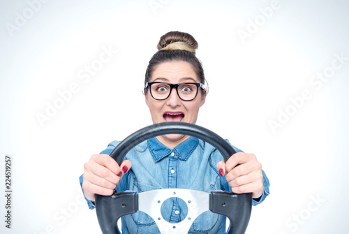 Valokuva  Happy screaming young girl with glasses and car steering wheel, front view, auto