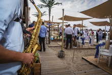 Saxophonist Plays A Wedding Party On The Beach. A Musician Playing A Classic Beach Party Instrument.