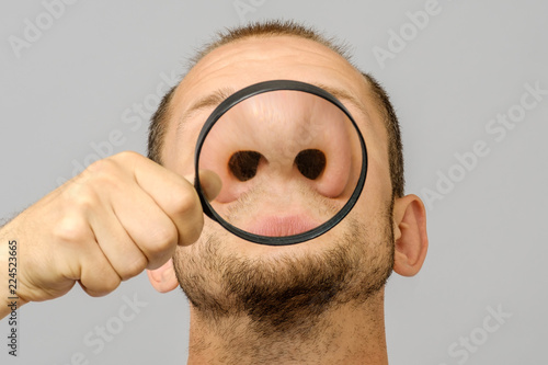 Fototapeta Portrait of caucasian man with magnifier makes fun face obraz