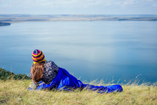 Tourist Woman Hiker Wrapped Up In A Blue Sleeping Bag On A Grass Lake Background Mountains