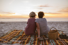 Young Lesbian Couple Watching A Romantic Sunset At The Beach