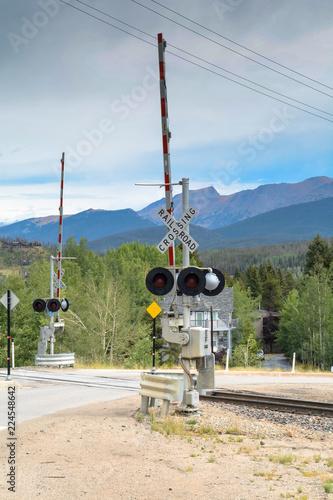 Fotografia, Obraz  Rail road crossing with mountain landscape