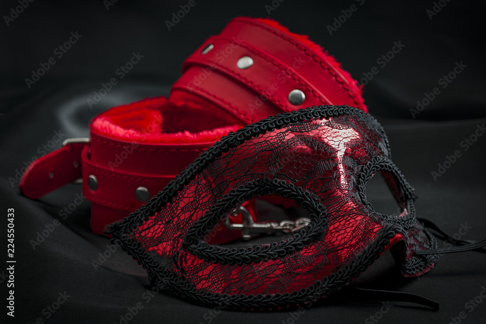 Fototapeta BDSM, bondage play, fetish wear and kinky sex toy concept with close up on erotic mask and red handcuffs isolated on black silk background
