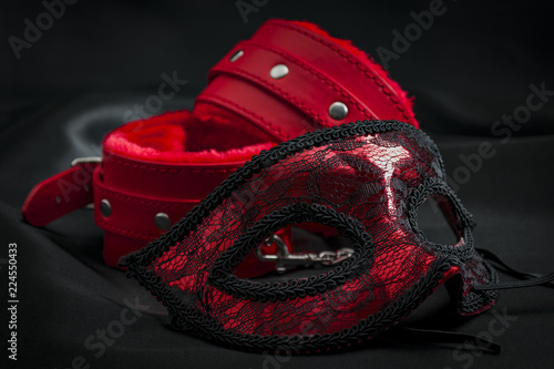 Fototapeta BDSM, bondage play, fetish wear and kinky sex toy concept with close up on erotic mask and red handcuffs isolated on black silk background obraz