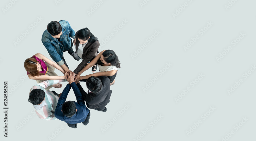 Fototapeta Top view of people in team stack hands together as unity and teamwork in office. young Asian team and group togetherness collaboration