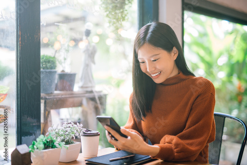 Fotografia  Young Asian woman using phone at a coffee shop happy and smile.