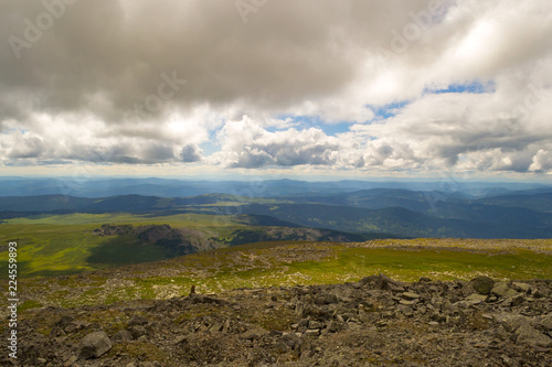 Landscape of green valley flooded with light with lush green grass, mountains, covered with stone and hills, a fresh summer day under a blue sky with white clouds and sun rays in Altai mountains