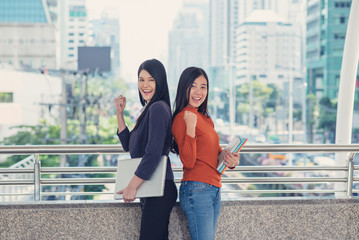 Fototapeta Two happy Asian women who succeed in the city.