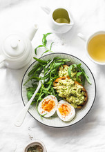 Healthy Breakfast Or Snack - Boiled Egg, Arugula Salad And Avocado Toast On A Light Background, Top View