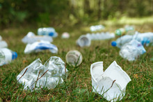 A Pile Of Plastic On Green Grass, A Problem In The Natural Environment, Pollution Of Nature Is Not Decomposing Plastic. Protection Of Nature. Copy Space