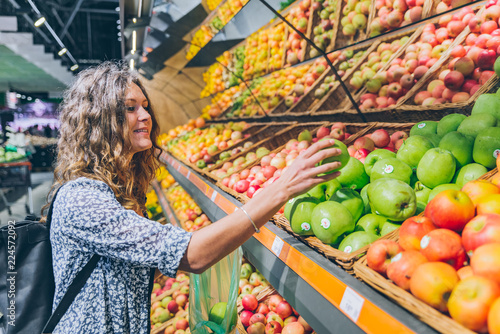 young adult woman choosing apples in grocery store