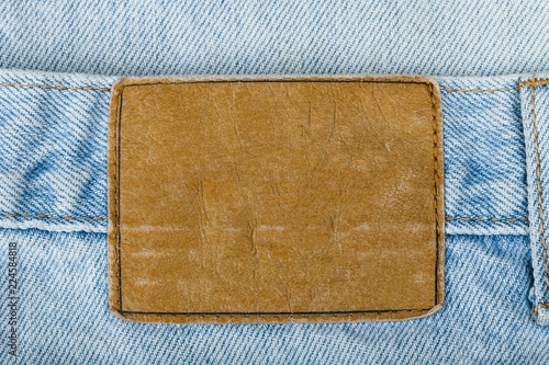 Fotografia  Blank Leather Jeans Label Sewed on a Blue Jeans