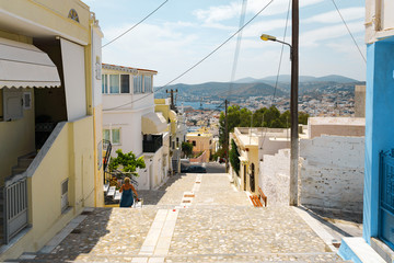 Fototapeta Сozy narrow streets of the old resort European town in a summer sunny day. Low-rise buildings of local residents, small cafes and hotels. Ermoupolis town on Syros island, Cyclades, greece.
